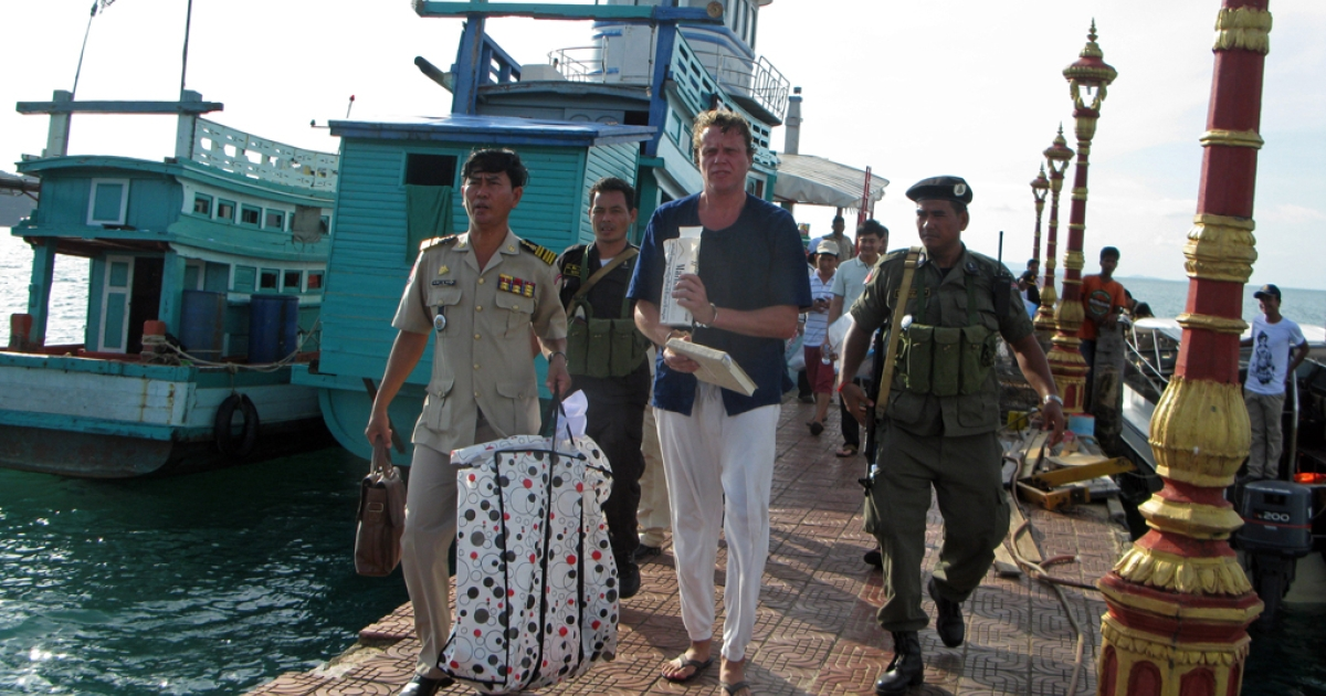 Russian tycoon Sergei Polonsky (C) walks along with police officers after his arrest in Sihanoukville, southern Cambodia, on November 11, 2013.</p>