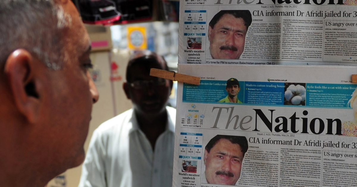A man reads newspapers bearing photographs of Pakistani Dr. Shakil Afridi, recruited by the CIA to help find Osama bin Laden, at a newsstand in Karachi on May 25, 2012.</p>