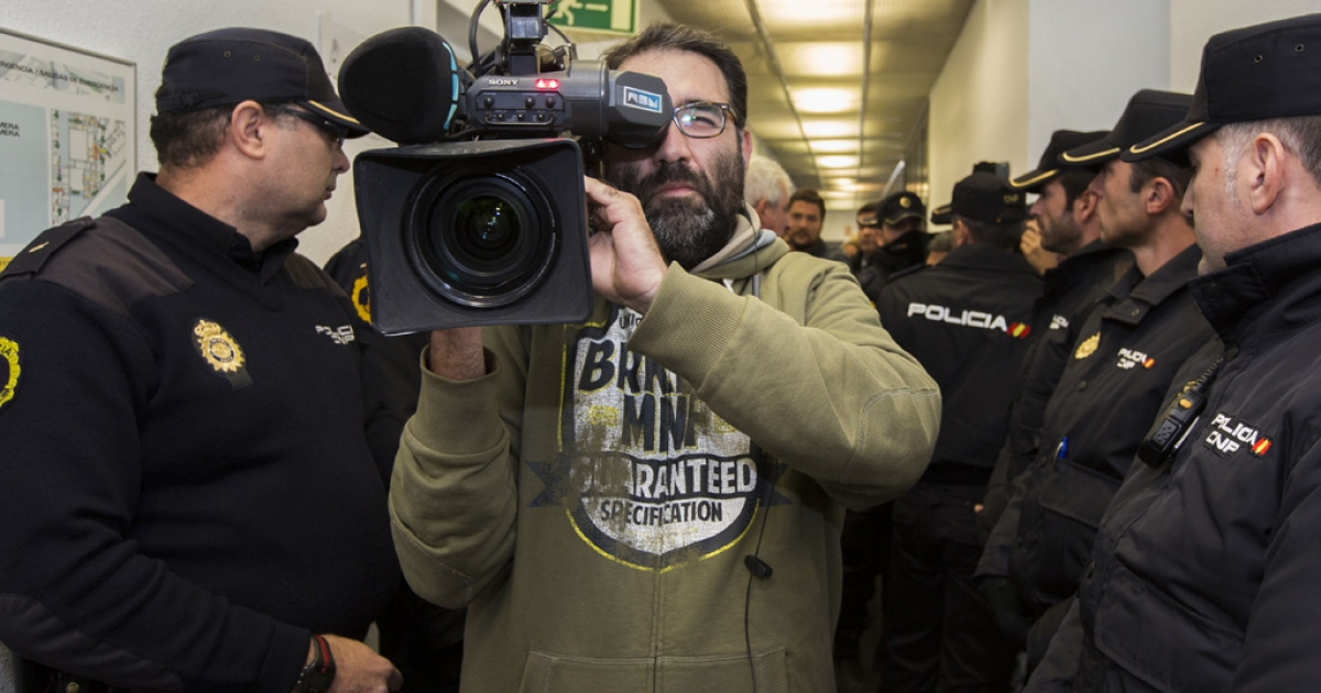 A man films as police officers expel workers of Spanish television station Channel 9, part of Valencia broadcaster RTVV, from the company's headquarters on November 29, 2013, following the closure of RTVV. The debt-laden Spanish television station went abruptly off the air, apparently cut off by authorities as laid-off staff protested live in defiance of orders to shut it down.</p>