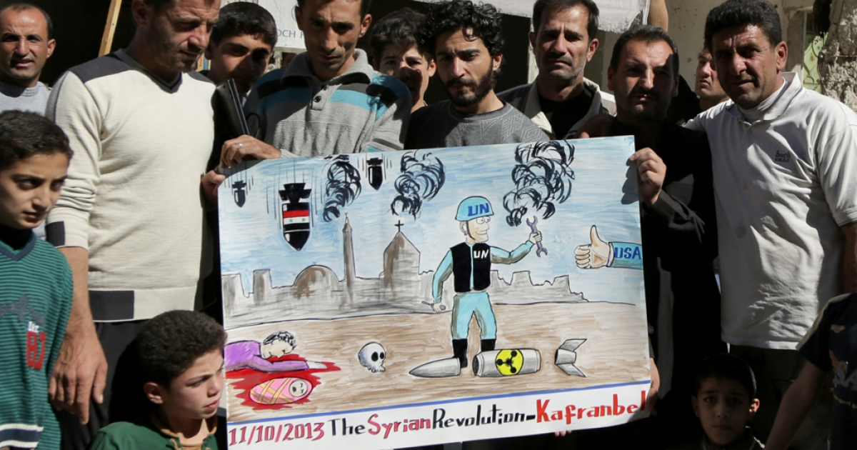 Syrian anti-government protestors hold a poster depicting a inspector from the Organisation for the Prohibition of Chemical Weapons (OPCW) during a demonstration to call for an international action against the Damascus regime on October 11, 2013.</p>