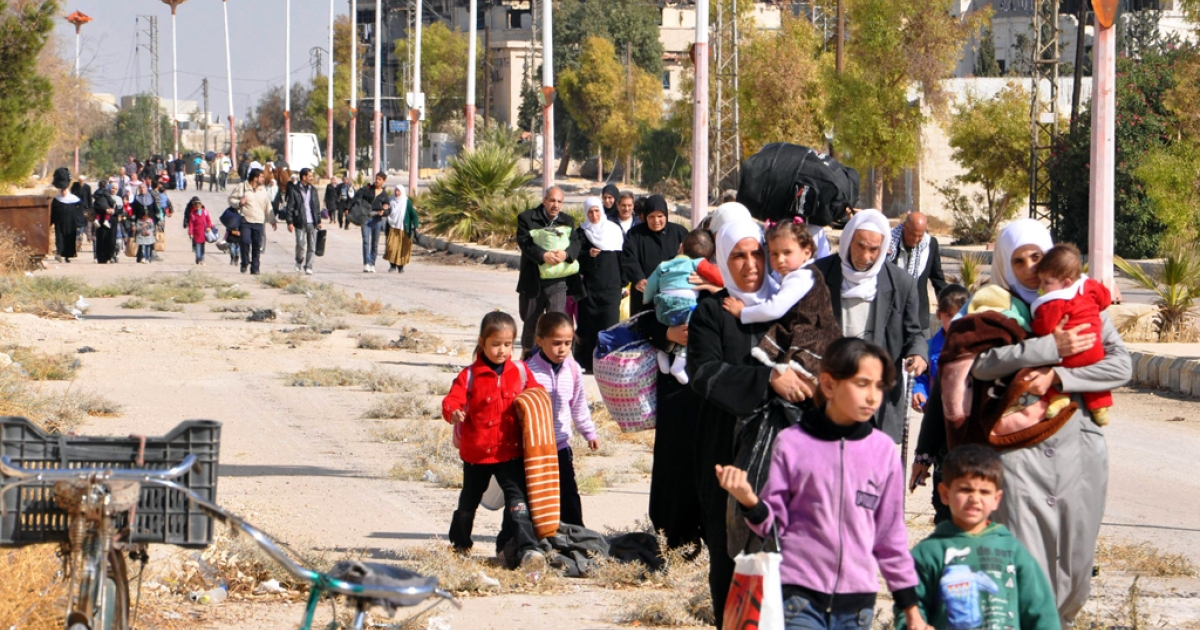 Syrian civilians evacuate the war-battered suburb of Damascus, Moadamiyet al-Sham, with the help of the Social Affairs Ministry, as fighting between pro-government troops and rebel fighters continues in districts of the capital, on October 29, 2013.</p>