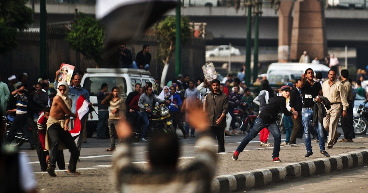 Egyptian supporters of the military-backed regime (background) throw stones towards anti-regime protesters during clashes in Cairo's Tahrir Square on Nov. 19, 2013.</p>