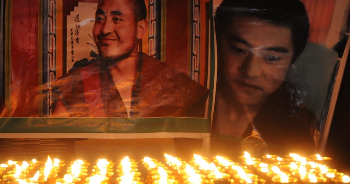 Portraits of Jamyang Palden (L), in his thirties from Rebkong and Lobsang Tsultrim, 20, from Ngaba, both from Tibet's Amdo region and who died by setting themselves on fire in protest, are seen in front of lit butter lamps during a vigil for Tibetans who have immolated themselves in protest against Chinese rule in Tibet, in McLeod Ganj on March 17, 2012.  A Spanish court has issued arrest warrants for five senior Chinese officials over genocide claims in Tibet.</p>