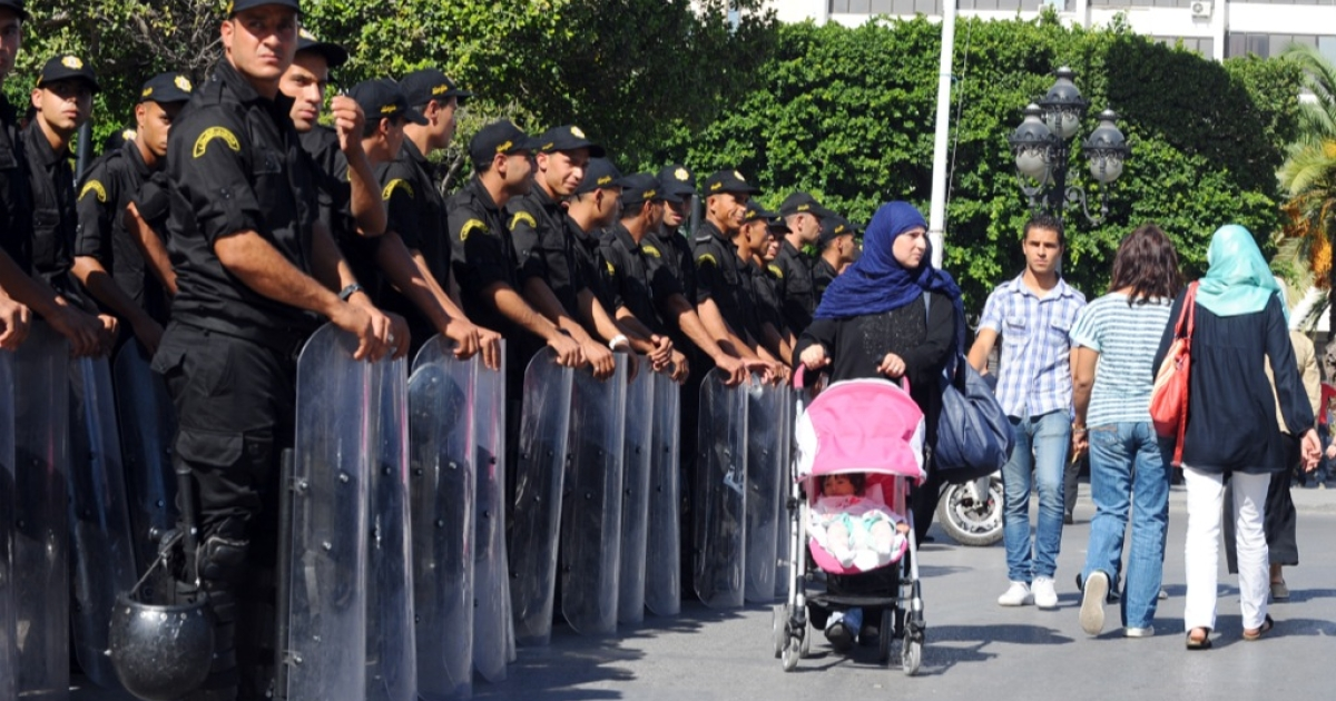 Tunisian people walk past security forces outside the Interior ministry on Tunis' central Habib Bourguiba Avenue where a demonstration takes place on October 23, 2013 to demand the resignation of Tunisia's Islamist-led government, ahead of a national dialogue aimed at ending months of political deadlock.</p>