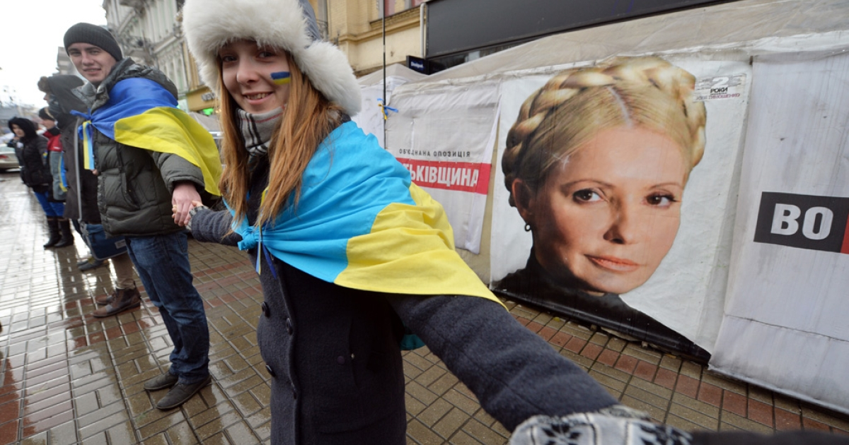 Ukrainian students stand hand-in-hand to create a human chain symbolizing the unity of Ukraine with the EU in front of the tents set up by supporters of Yulia Tymoshenko in Kiev on November 2013.</p>