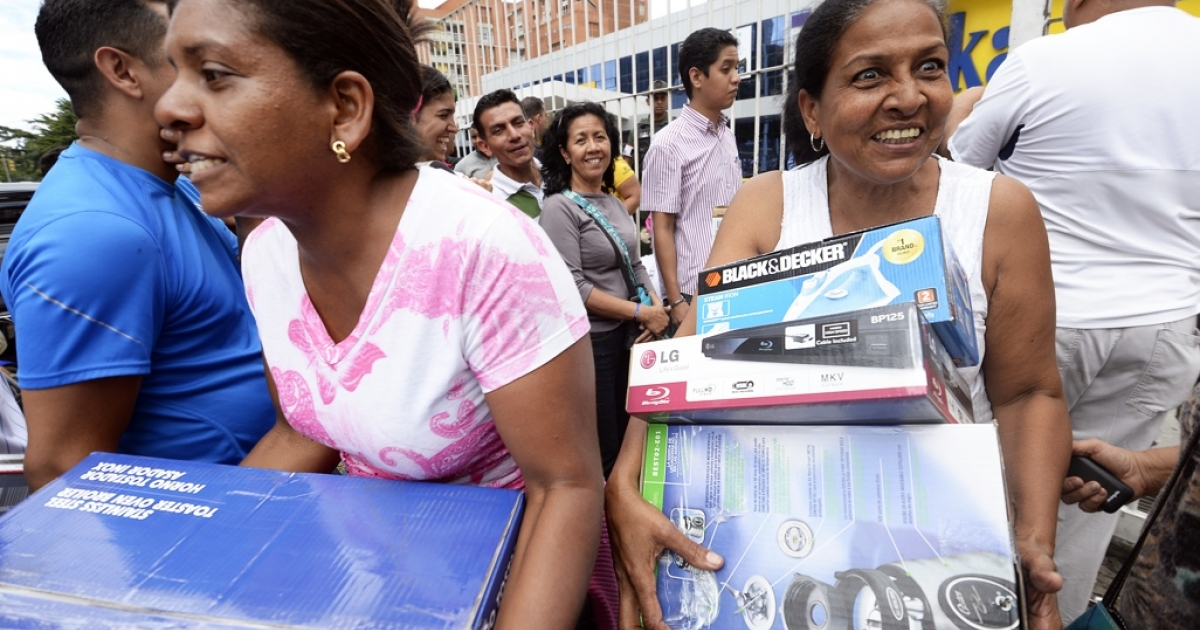 Shoppers loaded with purchases leave a Daka store in Caracas on Nov. 9. Venezuelan President Nicolas Maduro ordered the state occupation appliances stores accused of hiking prices.</p>