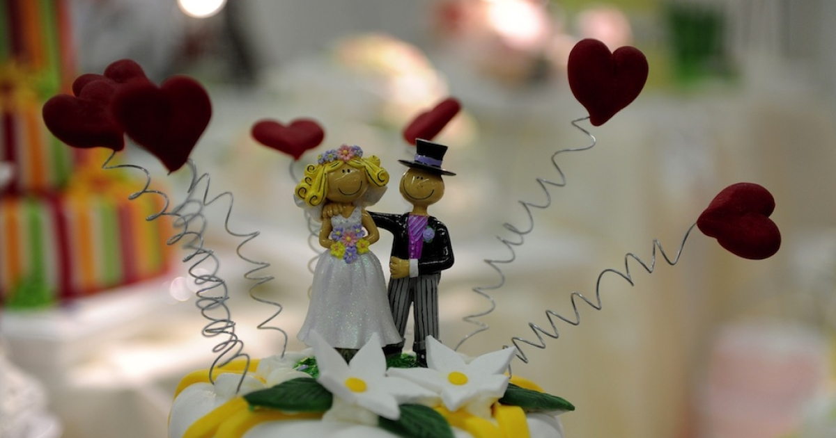 Bride and groom figurines decorate a wedding cake displayed at a wedding fair in the German city of Essen on Jan. 8, 2012.</p>