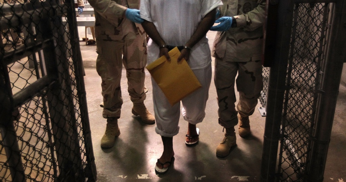 U.S. Navy guards escort a detainee after a 'life skills' class held for prisoners at Camp 6 in the Guantanamo Bay detention center on March 30, 2010 in Guantanamo Bay, Cuba. U.S. President Barack Obama pledged to close the facility by early 2010 but has struggled to transfer, try or release the remaining detainees from the facility, located on the U.S. Naval Base at Guantanamo Bay, Cuba.</p>
