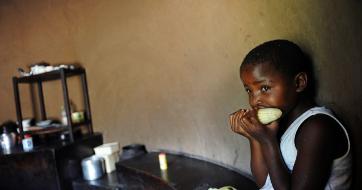 A child eats maize at home in Domboshava, 60km north of Harare, on March 15, 2013. UN officials said in October than more than 2 million Zimbabweans might need food assistance in 2014 because of a grain shortage.</p>