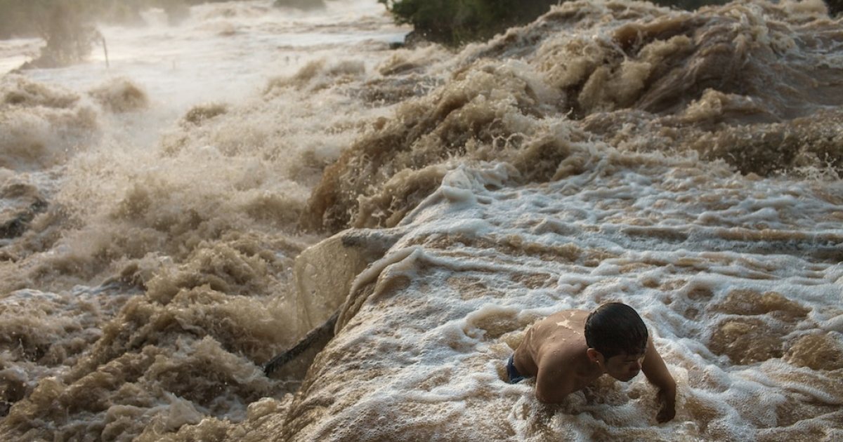 A fisherman fights the current of Khone Phapheng falls to clean debris from a