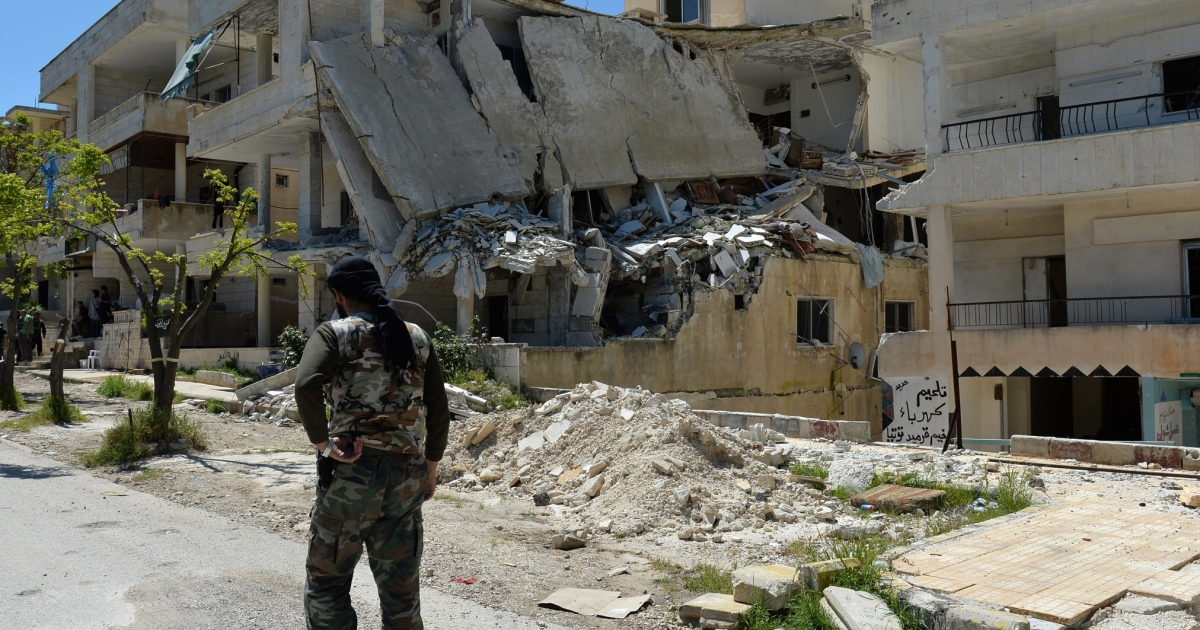 A Syrian rebel walks past a destroyed building in Salma in the coastal province of Latakia on April 26, 2013.</p>