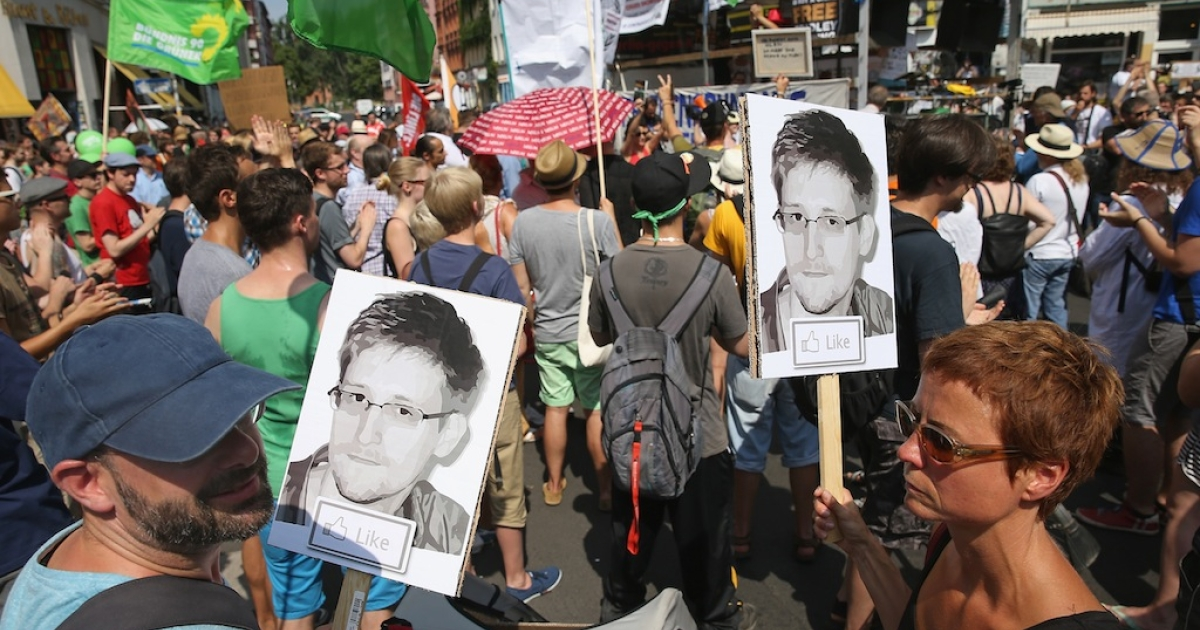 Participants demonstrate in support of former NSA employee Edward Snowden at a protest march against the electronic surveillance tactics of the NSA on July 27, 2013 in Berlin.</p>