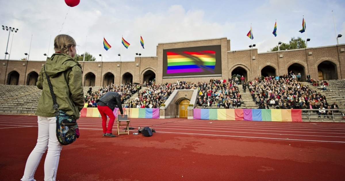 People sing the Russian National Anthem at the Stockholm Olympic Stadium on October 6, 2013 while raising rainbow flags in solidarity with the Russian LGBT community. A project called 'Live and Let Love' will use footage from the event to be cut together with other singers and musicians from around the world to make a video film that will be shown on YouTube ahead of the winter Olympic games in Sochi.</p>