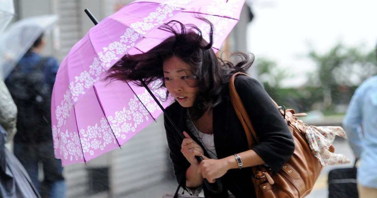 A woman walks against strong wind and rain in Tokyo from Typhoon Wipha on October 16, 2013.</p>