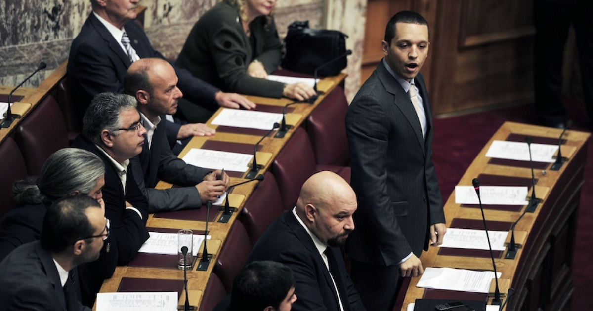 Golden Dawn party spokesman Ilias Kassidiaris speaks next to the party's lawmaker Ilias Panagiotaros at the Greek parliament on October 16, 2013, prior to the vote to lift the immunity from prosecution of six lawmakers from the Golden Dawn party.</p>