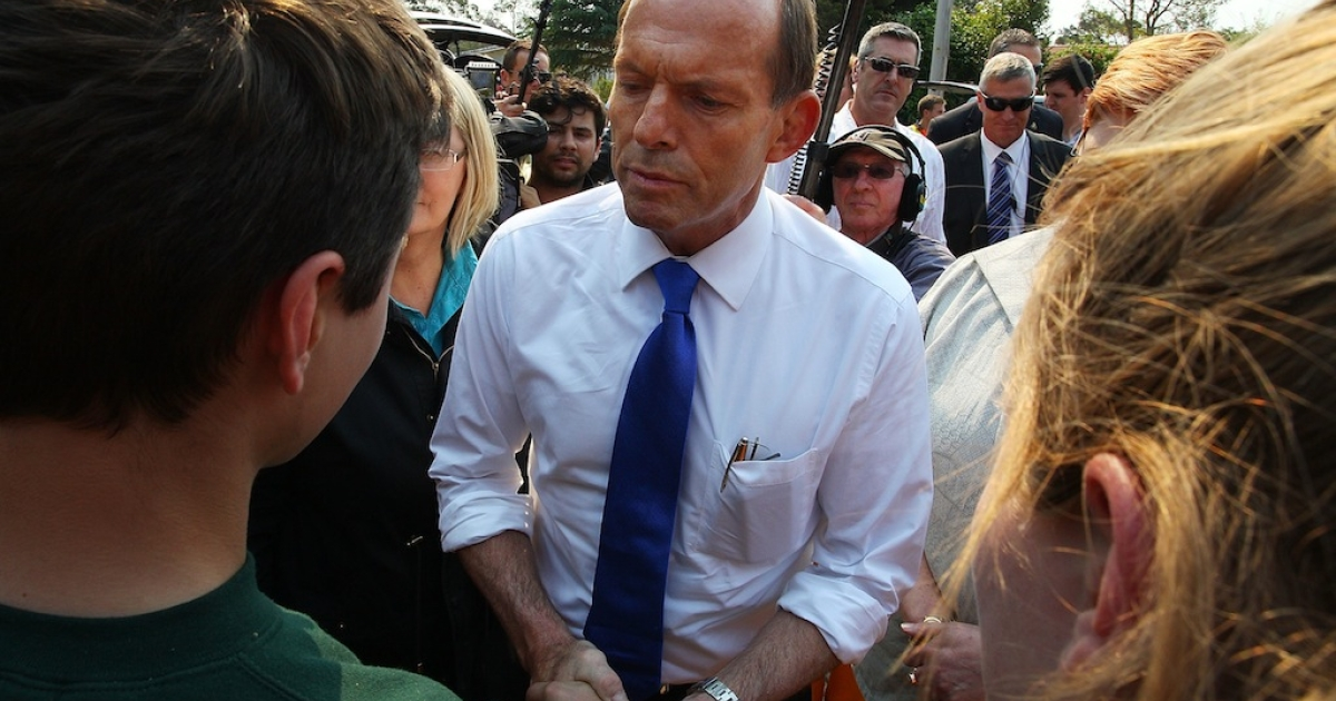 Prime Minister Tony Abbott greets locals Ashley More and Spephanie Schoer at Winmalee Fire Station on October 18, 2013 in Winmalee, Australia. Abbott has staunchly maintained that climate change has not played a role in the bushfires that are sweeping New South Wales.</p>