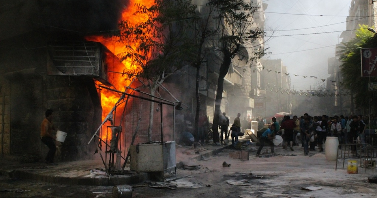 People use buckets to try and extinguish a fire that ignited at a local fuel station in the Bustan al-Qasr neighbourhood of Syria northern city of Aleppo on October 20, 2013.</p>