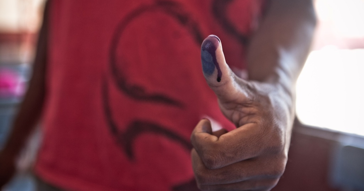 A man shows his inked finger after voting at a polling station on October 25, 2013 in Tamatave, on the eastern coast of Madagascar.</p>
