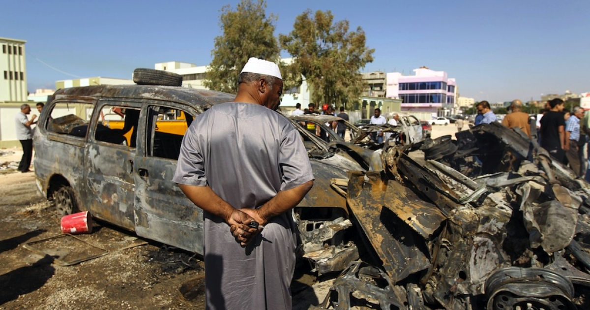 Benghazi residents gather at the site of a car blast in the parking lot of school used as an electoral office on October 26, 2013.</p>