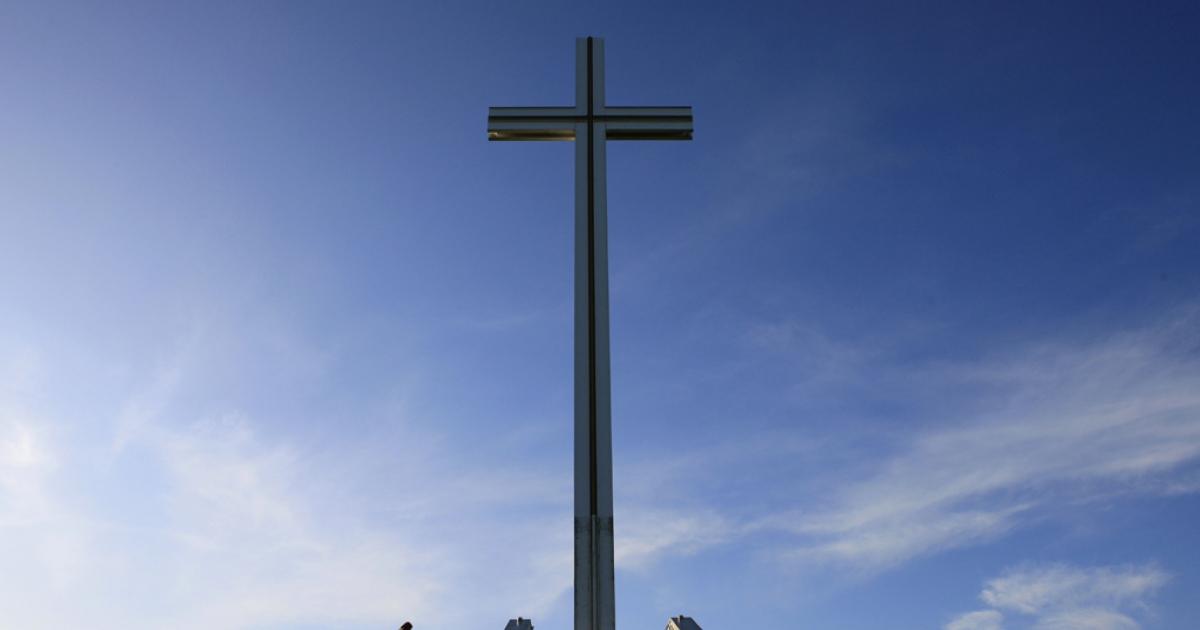 A man walks past the Papal Cross in Phoenix Park, in Dublin, Ireland.</p>