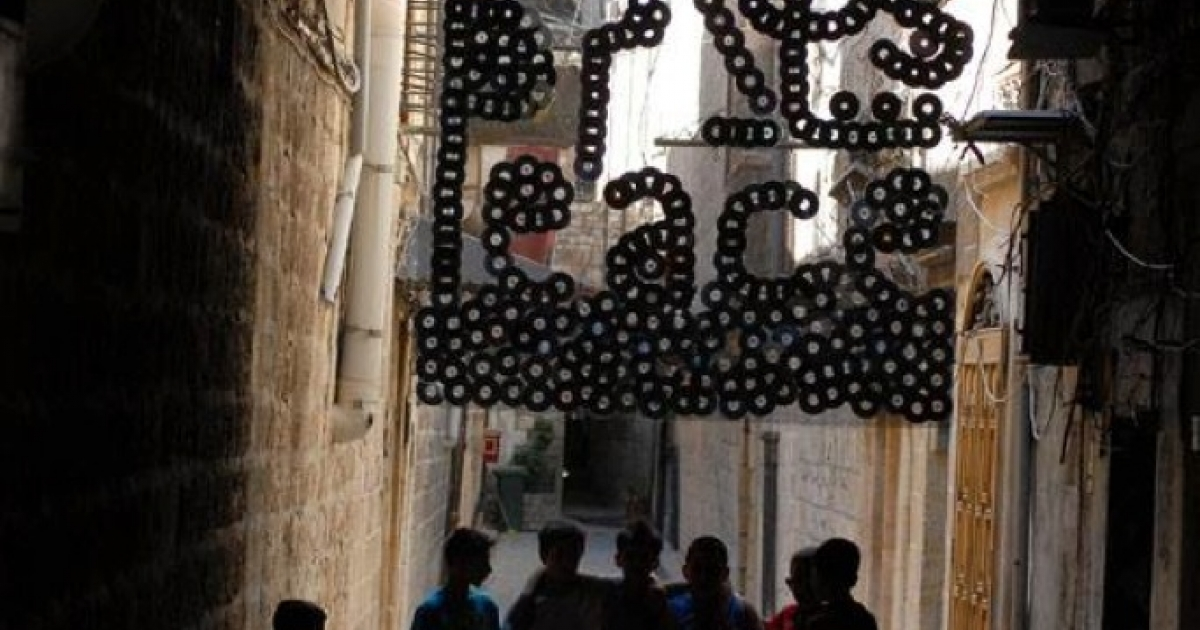 Children stand on July 20, 2013 in the Old City of Aleppo, under an installation that was part of Issa Touma's Art Camping initiative.</p>