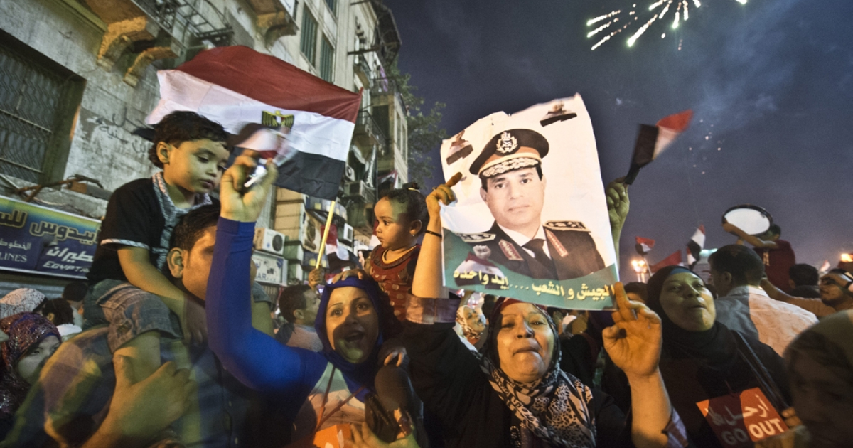 People celebrate at Tahrir Square with a portrait of Army chief Abdel Fattah al-Sisi after a broadcast confirming that the army will temporarily be taking over from the country's first democratically elected president Mohamed Morsi on July 3, 2013 in Cairo.</p>