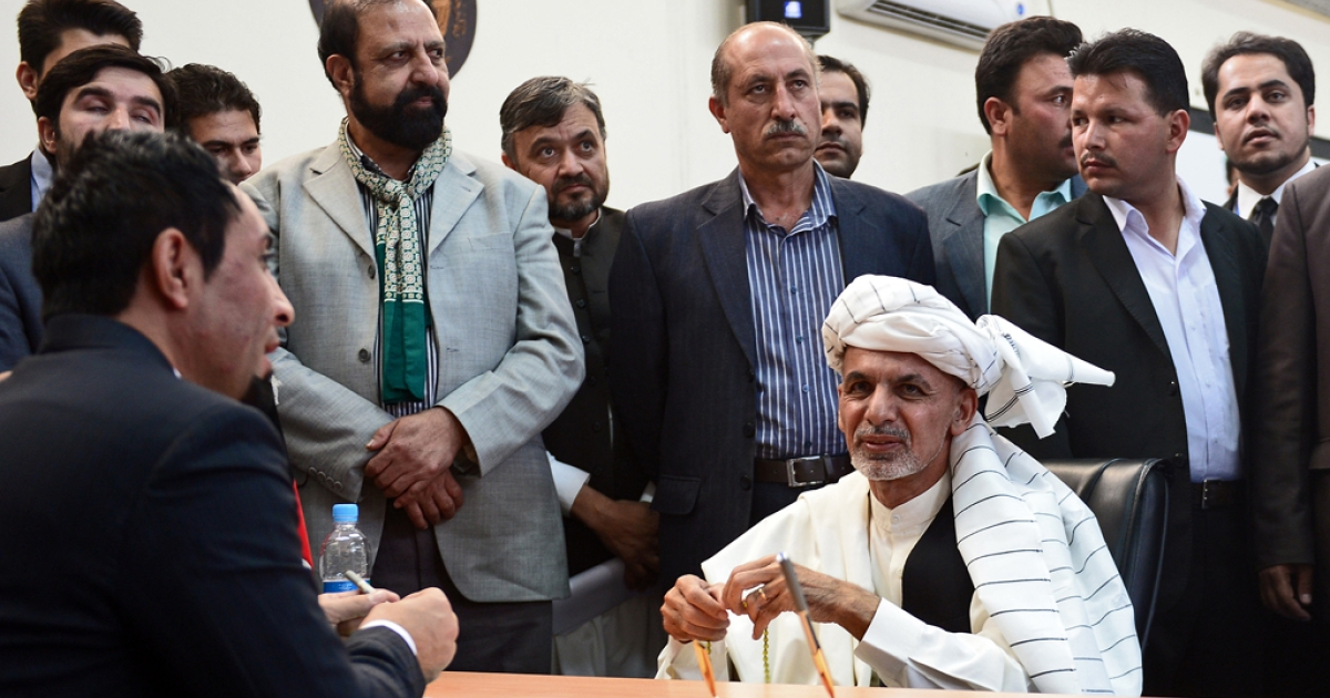 Afghan politician and former finance minister, Ashraf Ghani (R), looks on as he registers his name for the forthcoming presidential elections at the Independent Election Commission (IEC) in Kabul on October 6, 2013.</p>