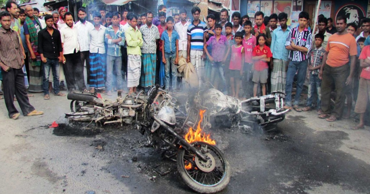Bangladesh villagers look at a motor bike set alight by opposition supporters during a nationwide strike called by the opposition Bangladesh Nationalist Party (BNP) in Ishurdi, some 200 kms from Dhaka on October 27, 2013</p>