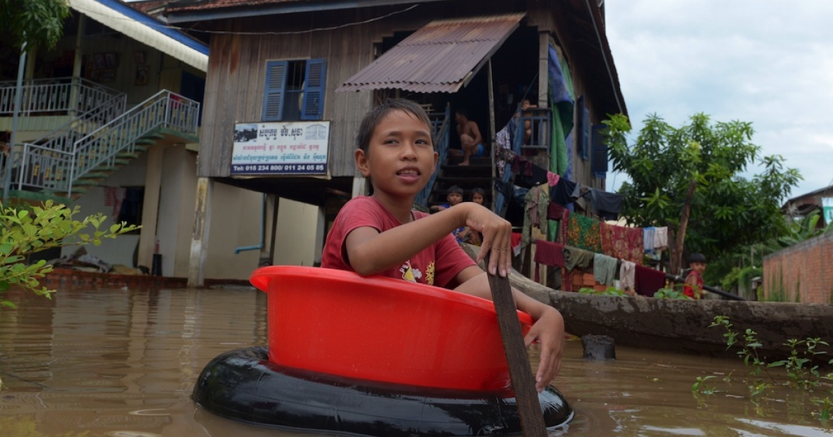 A Cambodian boy rows through flood waters in front of his house on the outskirts of Phnom Penh on September 27, 2013.</p>
