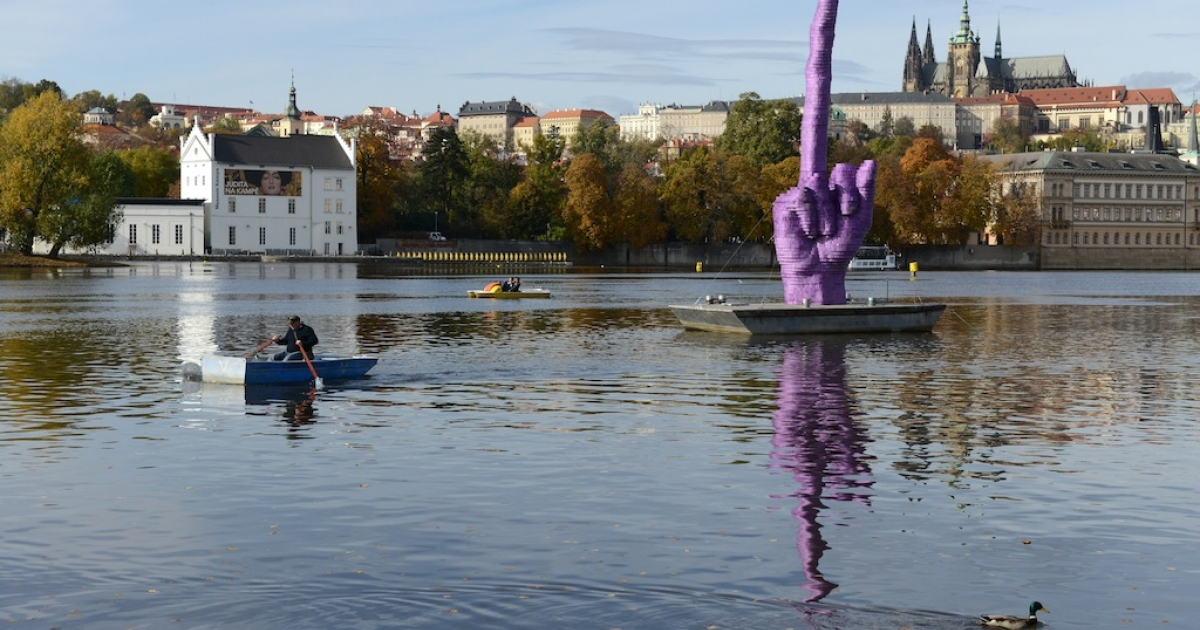 People sailing on Vltava River by the giant purple middle finger sculpture by Czech artist David Cerny on October 21, 2013 in Prague. This artwork installed today, four days before the Czech early general election, on the Vltava River is addressed to Czech president Milos Zeman who's residency is at Prague Castle (in background).</p>