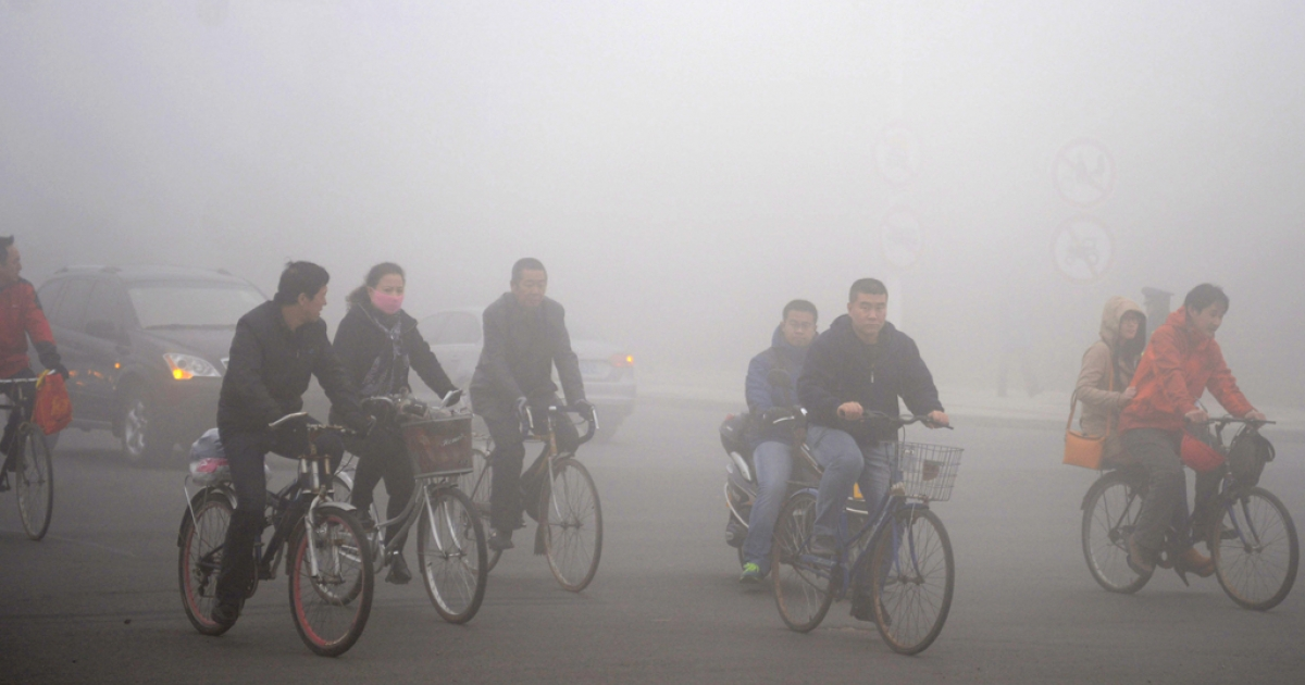 (CHINA OUT) Cyclists ride along a road as heavy fog engulfs the city on October 21, 2013 in Daqing, China. Heavy fog has been lingering in northeast China since Monday, disturbing the traffic, worsening air pollution and forcing the closure of schools.</p>