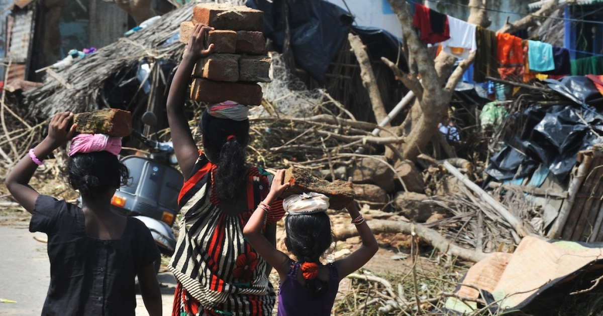 Indian children help their mother carry bricks to rebuild their damaged house following Cyclone Phailin in Gopalpur on October 14, 2013. Hundreds of thousands of people who fled India's strongest cyclone in 14 years returned home to scenes of devastation, as survivors stranded at sea during the storms were finally rescued.</p>