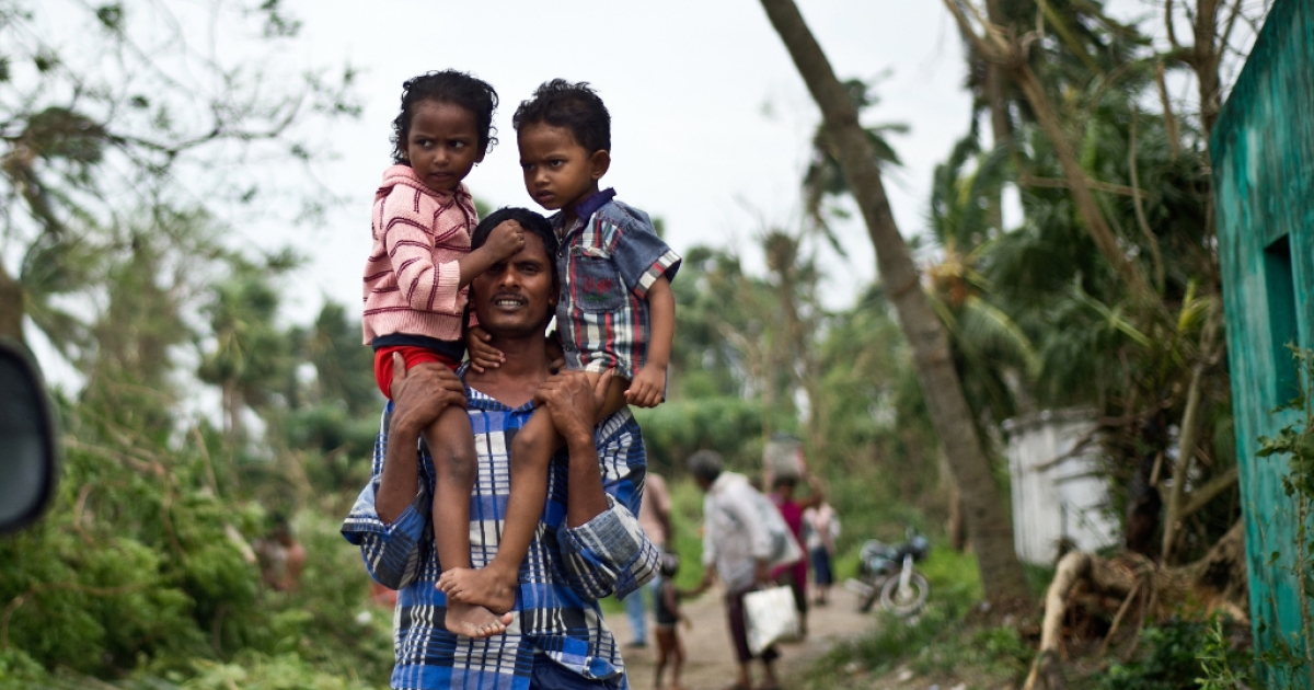 A displaced Indian man carries his children at Sonupur village around 15 kms from Gopalpur on October 13, 2013. Cyclone Phailin left a trail of destruction along India's east coast and up to seven people dead after the biggest evacuation in the country's history helped minimise casualties.</p>