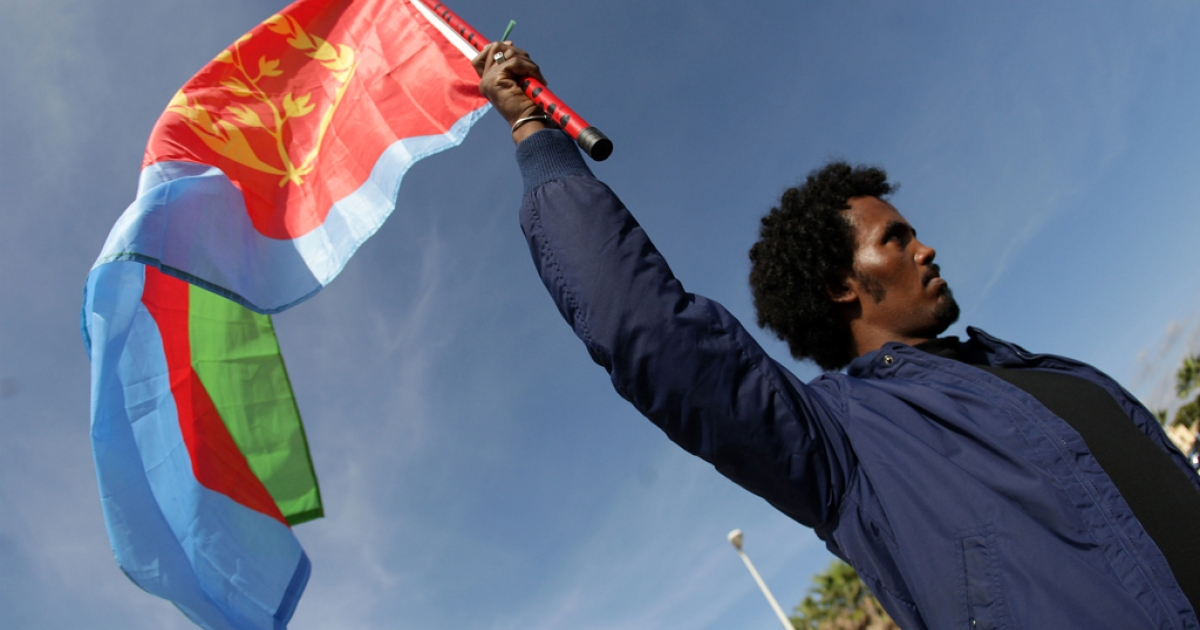 A man waves an Eritrean flag  on October 21, 2013 in the southern Sicilian city of Agrigento during a ceremony commemorating the migrants who drowned off the southern Italian islad of Lampedusa.</p>