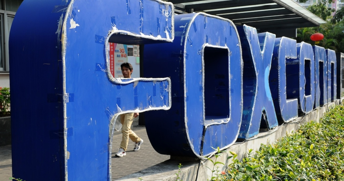 This picture taken on Feb. 22, 2013 shows a young man walking past a Foxconn recruitment center in the southern Chinese city of Shenzhen.</p>