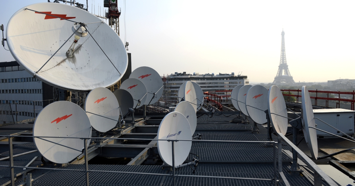 Antennas and satellite dishes, in front of the Eiffel tower in Paris, France.</p>