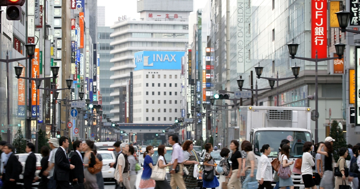 People walk across the street in the Ginza district of Tokyo, Japan in 2009.</p>