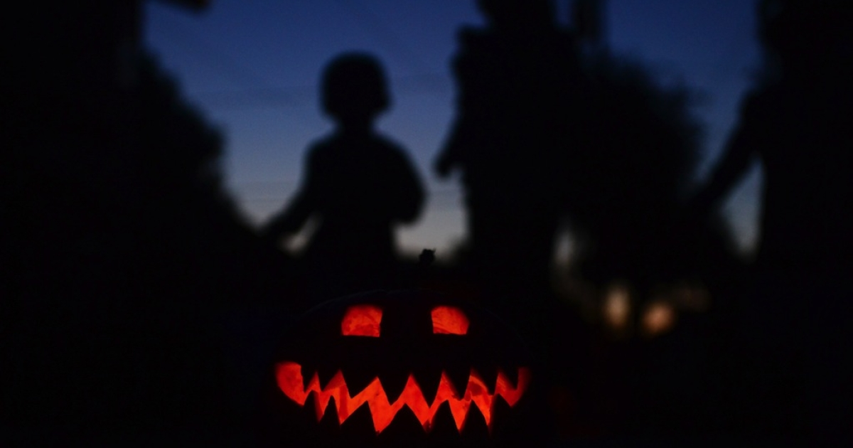 Children play behind a pumpkin carved and lit for Halloween on Oct. 30, 2013 in Monterey Park, California.</p>