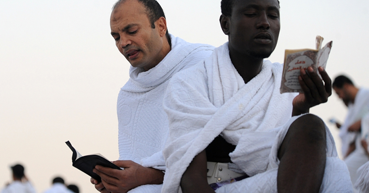 Muslim pilgrims read from a copy of the Koran as the pray on Mount Arafat, near the holy city of Mecca, ahead of the hajj main ritual, on October 14, 2013.</p>