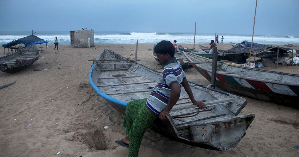 An Indian fisherman sits on his boat on a beach near Gopalpur in the eastern state of Orissa on Oct. 11, 2013. Authorities have asked fishermen to stay ashore as Cyclone Phailin barrels toward the coast.</p>