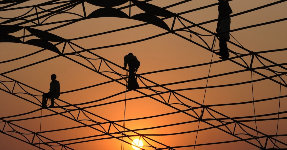 Indian labourers erect a temporary structure in Ahmedabad on November 13, 2011. A new film series examines the plight of the South Asian male.</p>