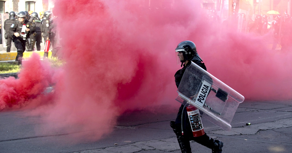 Riot police throw smoke grenades during clashes with students along Reforma Avenue in Mexico City on October 2, 2013.  Mexican students marched to commemorate the anniversary of the Tlatelolco massacre of university students.</p>