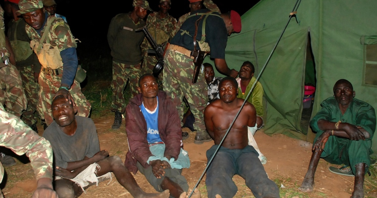 A picture taken on October 17, 2013 shows prisoners belonging to former Mozambican rebel movement Renamo sitting on the ground with government soldiers guarding them in Gorongosa.</p>