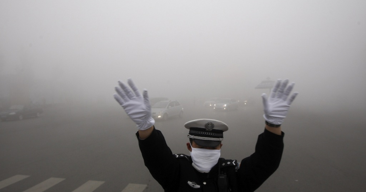 A policeman directs traffic in thick smog in China's northeastern city of Harbin on Oct. 21, 2013.</p>