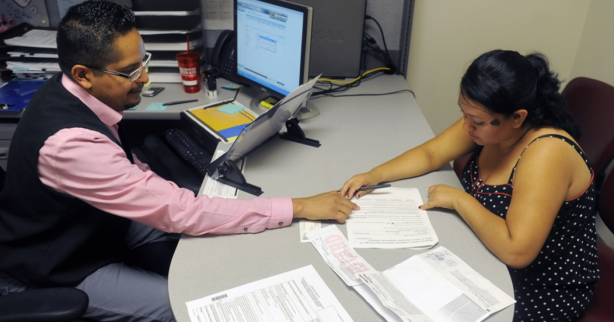 Enrollment Specialist Horacio Castaneda, left, helps Rosa Ayala Cruz, right, apply for health benefits at the Denver Health Westside Family Health Center on Oct. 1, 2013 in Denver, Colo.</p>