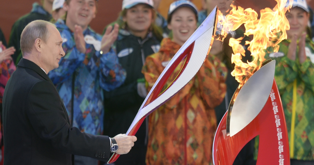 Russian President Vladimir Putin lights a torch in Moscow, Oct. 5, 2013.</p>