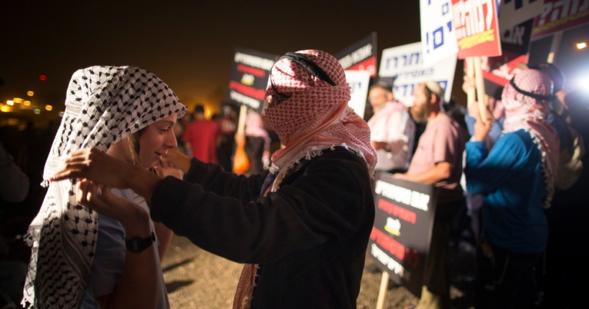 Israeli youths wear keffiyehs, traditional Palestinian scarfs, as right wing Israelis demonstrate against the release of 26 Palestinian prisoners on Oct. 29, 2013 outside Ofer military prison on the outskirts of Jerusalem. The prisoners are to be freed as part of the terms of renewed US-brokered peace talks.</p>