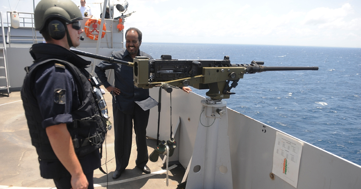 Somali President Hassan Sheikh Mohamud (C) stands onboard a Dutch Amphibious Assault warfare ship part of the EU Naval Force off the coast of Mogadishu on September 5, 2013. The ship, part of the EU naval taskforce whose role is to thwart any potential pirate attacks in the region.</p>