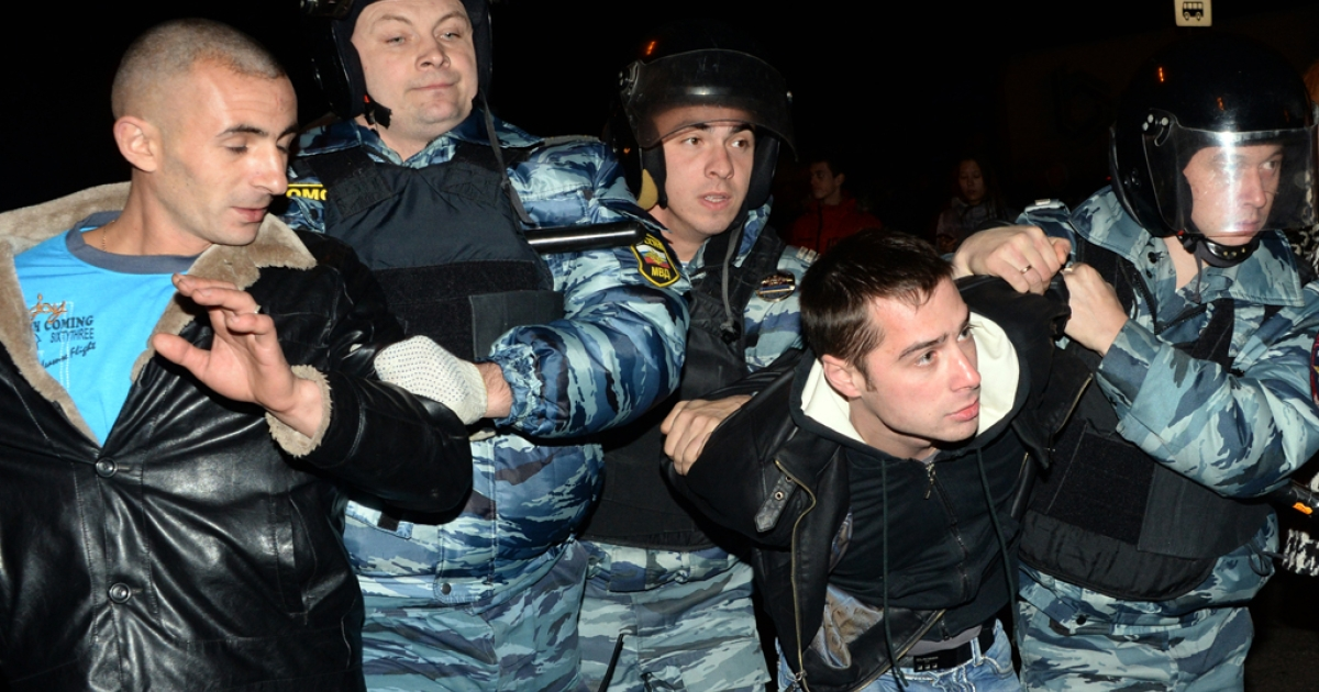 Russian riot policemen detain two men at the end of a rally in Moscow's southern Biryulyovo district on October 13, 2013.</p>