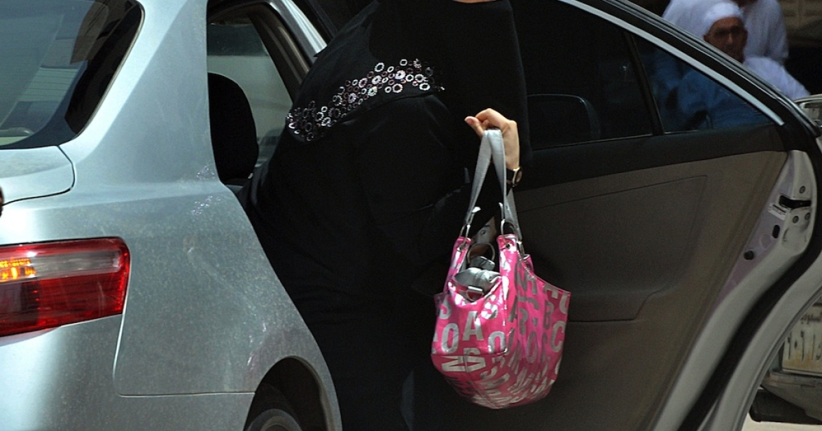 A Saudi woman gets out of a car after being given a ride by her driver in Riyadh on May 26, 2011.</p>